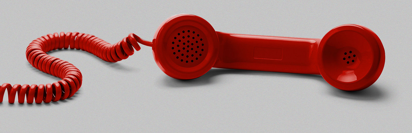 Red, old-style phone handset and cord, against a gray background